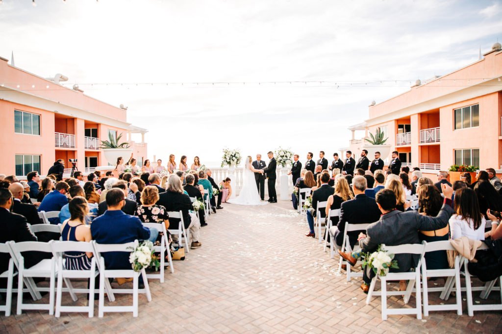 Waterfront Romantic Outdoor Wedding Ceremony and Decor, Rooftop Vow Exchange on Balcony, Decorated with Lush Floral Arrangements, with Ivory Roses, White Hydrangeas, and Greenery | Florida Beachfront Destination Wedding Venue Hyatt Regency Clearwater Beach | Tampa Bay Wedding Planner Special Moments Event Planning | St. Petersburg Florist Bruce Wayne Florals | Florida Beachfront Destination Wedding Venue Hyatt Regency Clearwater Beach | Tampa Bay Wedding Planner Special Moments Event Planning | St. Petersburg Florist Bruce Wayne Florals