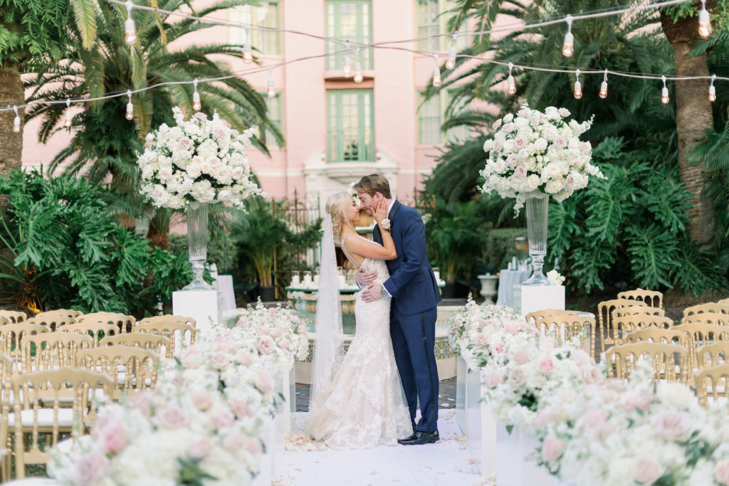 Romantic Florida Bride and Groom Kiss Intimate Embrace at Outdoor Garden Wedding Ceremony, Decorated with Elegant Tall Rose Floral Arrangements, Ivory, Blush Pink, and White Flowers, Gold Napoleon Chairs, Bride Wearing Eve of Milady Kleinfeld Bridal Dress, Groom in Navy Suit with Champagne Rose Boutonniere | Tampa Bay Wedding Planner Parties A'La Carte | Tea Garden Ceremony at Florida Wedding Venue and Historic Resort The Vinoy Renaissance in Downtown St. Petersburg