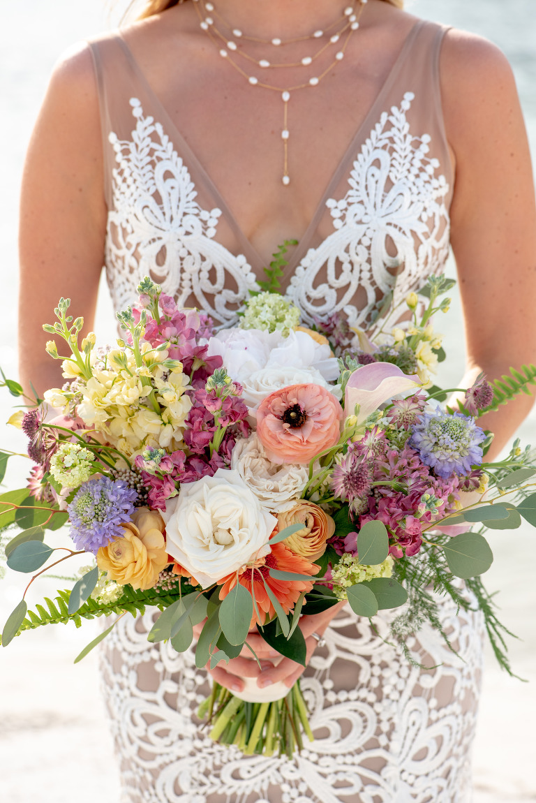 Tampa Bay Bride holding Springtime Vibrant Floral Bouquet, with Peach, Purple, Pink, Yellow, Purple and Orange Florals, Bride wearing Boho Chic Made with Love Bridal Wedding Dress