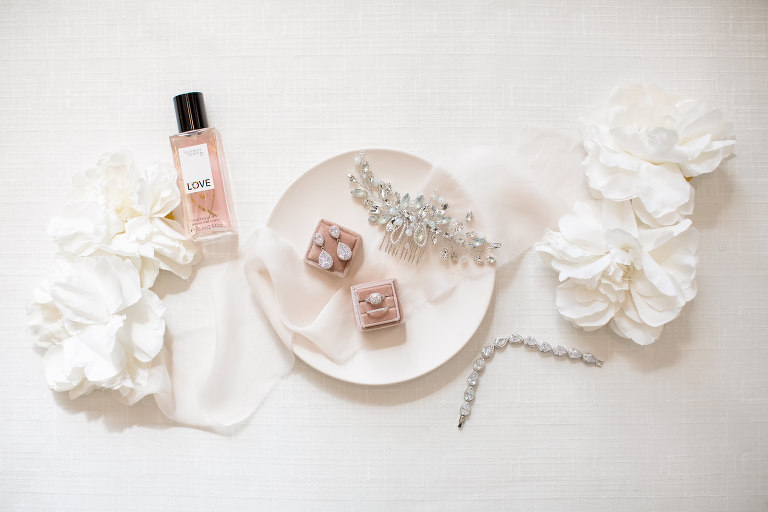 Wedding Accessories Photography Flay Lay | Rhinestone Bridal Hair Piece Comb | Blush Pink Velvet Ring Box with Square Diamond Cushion Cut Engagement Ring | Diamond Teardrop Chandelier Earrings and Tennis Bracelet