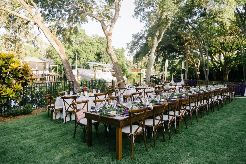 Romantic Outdoor Backyard Reception on the water, Long Wooden Feasting Tables with Farmhouse Chairs, Jeweled Tone Tablescape with Greenery Garland, Vibrant Pink Roses, Purple Linens, Gold Chargers | South Tampa Wedding Planner Breezin' Weddings | Beach Park Wedding Rentals Outside the Box Event Rentals | Tampa Bay Wedding DJ Breezin' Entertainment