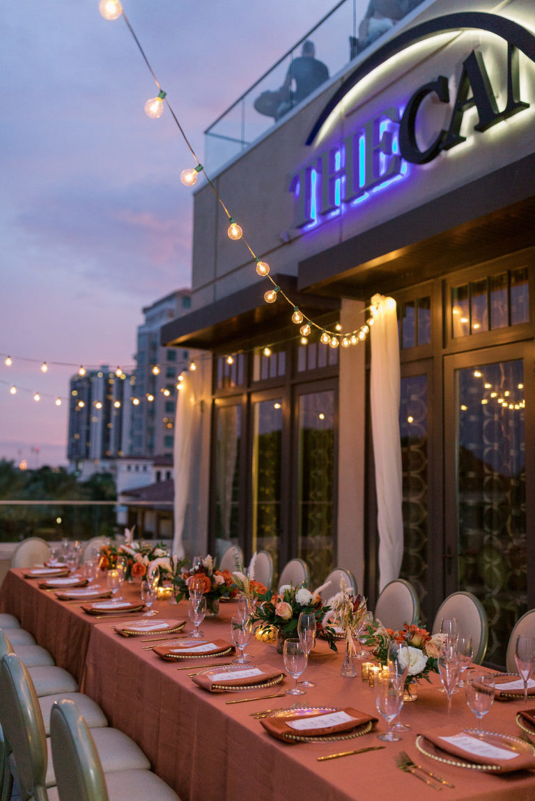 Outdoor Terrace Wedding Feasting Table at St. Pete Wedding Venue The Birchwood | Intimate Micro Wedding Elopement COVID Styled Shoot | Fall Autumn Wedding Inspiration | Hotel Terrace Reception with Canopy String Lights Orange Copper Wedding Table Linens | Gold Beaded Glass Chargers with Napkin and Menu Card and Gold Flatware | Wedding Centerpiece with Orange White and Peach Roses