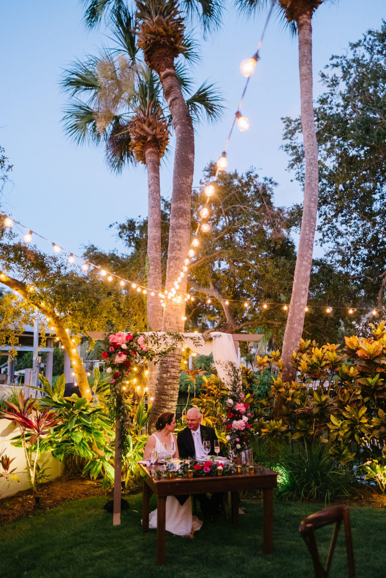 Modern, Outdoor South Tampa Backyard Wedding Reception and Decor, Florida Bride and Groom sit Under Wedding Arch with Jeweled Tone Florals | Tampa Bay Wedding Planner Breezin' Weddings | Wedding DJ Breezin' Entertainment | Outside The Box Event Rentals