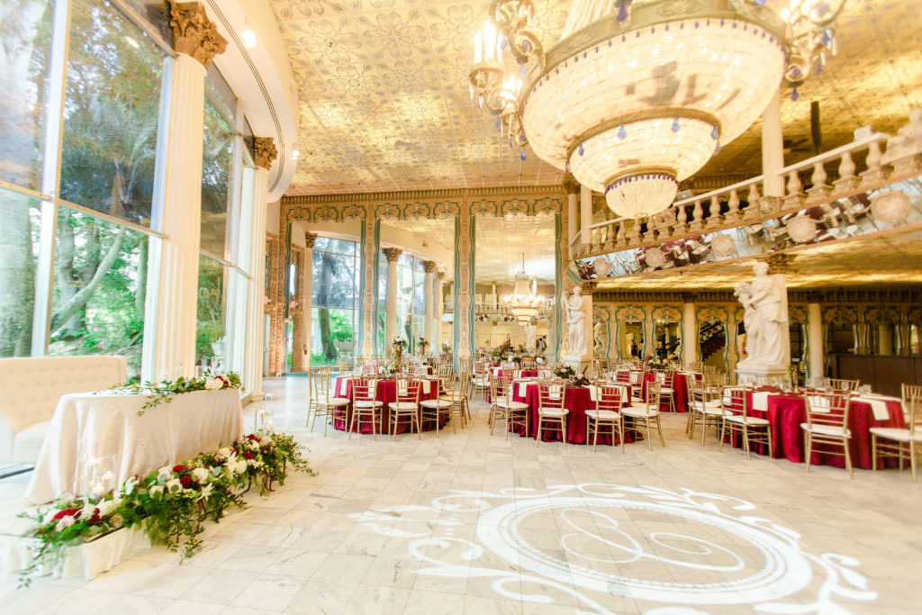 Clearwater Florida Fairy Tale Wedding Reception with Chandeliers and Monogram GOBO Dancefloor | Burgundy Deep Red Guest Table Linens with Gold Chiavari Chairs | Champagne Sweetheart Table with Loveseat and Greenery Garland with White and Burgundy Roses | Kapok Special Events