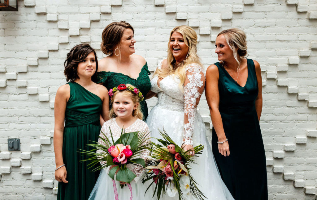 Bride Tampa Bay Wedding Planner Katy from Coastal Coordinating in Romantic Lace Illusion Long Sleeve Ballgown Wedding Dress, Bridesmaids in Emerald Green Mix and Match Dresses, Daughter Flower Girl in White Dress Holding Tropical Floral Bouquets with White Orchids, Palm Fronds and Pink Flowers