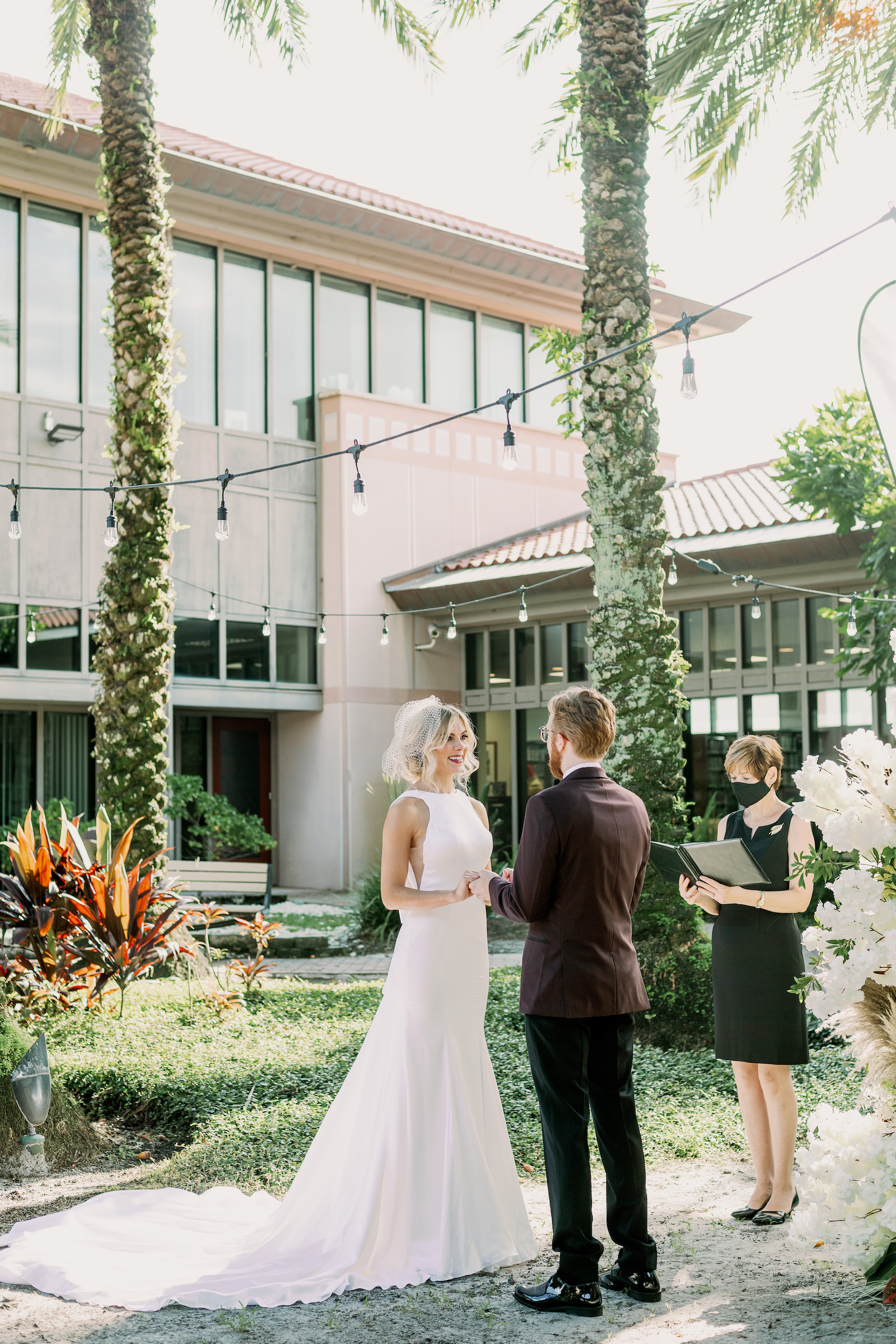 Bride and Groom Outdoor Atrium Intimate COVID Elopement Micro Wedding Ceremony at St. Pete Wedding Venue The Poynter Institute   LoAdoro Bridal Sleek Fitted Modern Wedding Dress Bridal Gown with Birdcage Veil from Tampa Bridal Shop Truly Forever Bridal   Groom in Modern Suit with Dark Red Maroon Jacket with Black Satin Lapel and Bow Tie   Tampa Wedding Officiant A Wedding With Grace