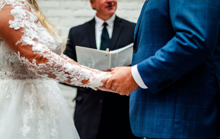 Tampa Bay Bride Katy Wedding Planner from Coastal Coordinating and Groom Exchanging Wedding Vows Holding Hands at Wedding Venue Oxford Exchange