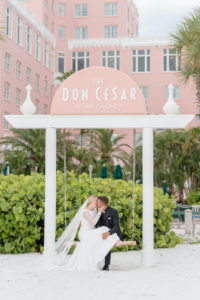 Romantic Bride and Groom on Swing on White Sand Beach of St. Petersburg Historic Wedding Venue The Pink Palace, Don Cesar   Styled Shoot