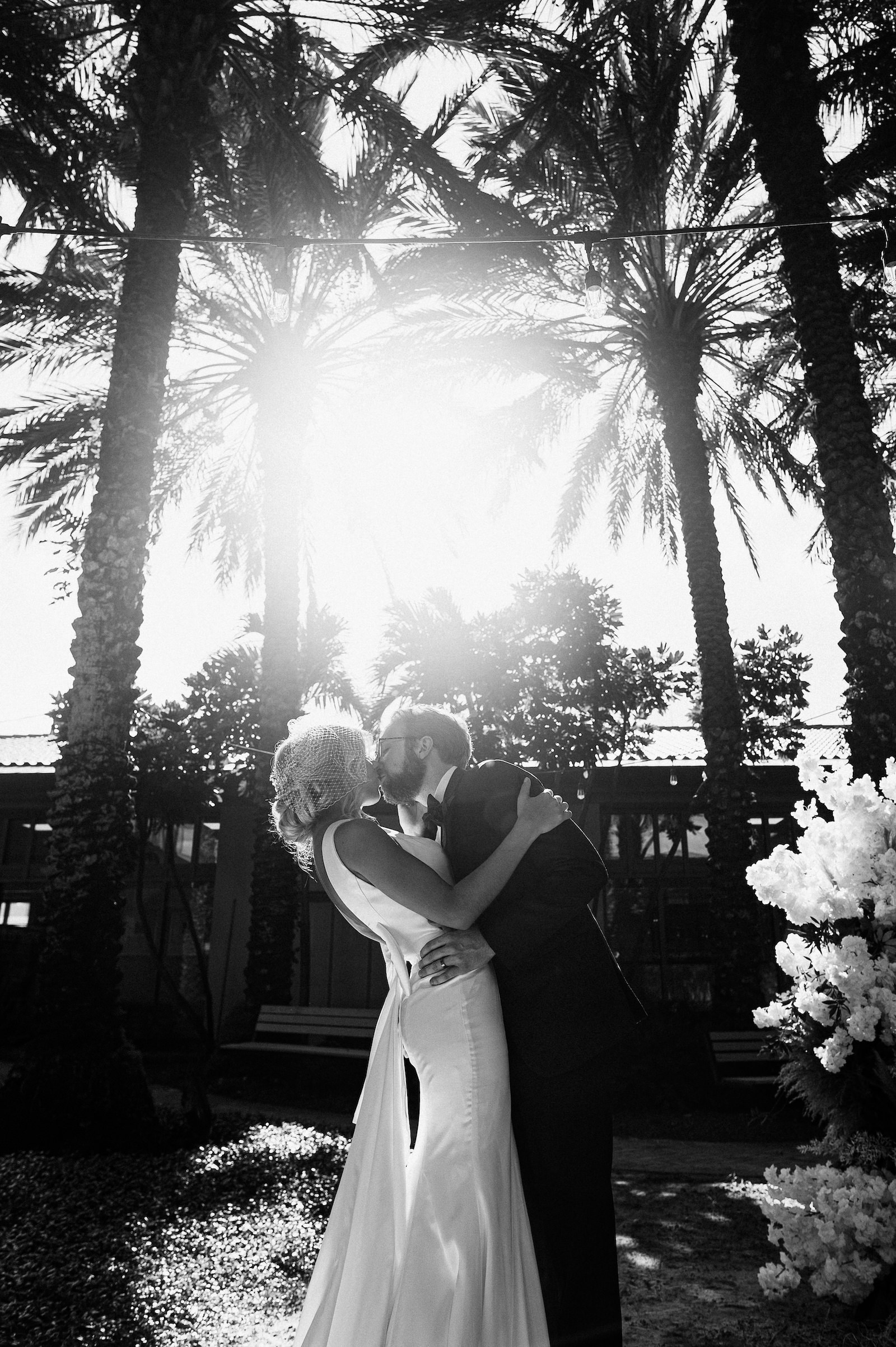 Bride and Groom Outdoor Atrium Intimate COVID Elopement Micro Wedding Ceremony at St. Pete Wedding Venue The Poynter Institute   LoAdoro Bridal Sleek Fitted Modern Wedding Dress Bridal Gown with Birdcage Veil from Tampa Bridal Shop Truly Forever Bridal   Black and White Wedding Photography with Sun Flare   Dewitt for Love Photography