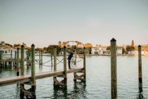 Romantic Intimate Bride and Groom on Waterfront Dock Kissing, Bride Holding Lush White, Ivory and Blush Pink Roses and Eucalyptus Floral Bouquet | St. Pete Boutique Hotel Wedding Venue Hotel Zamora