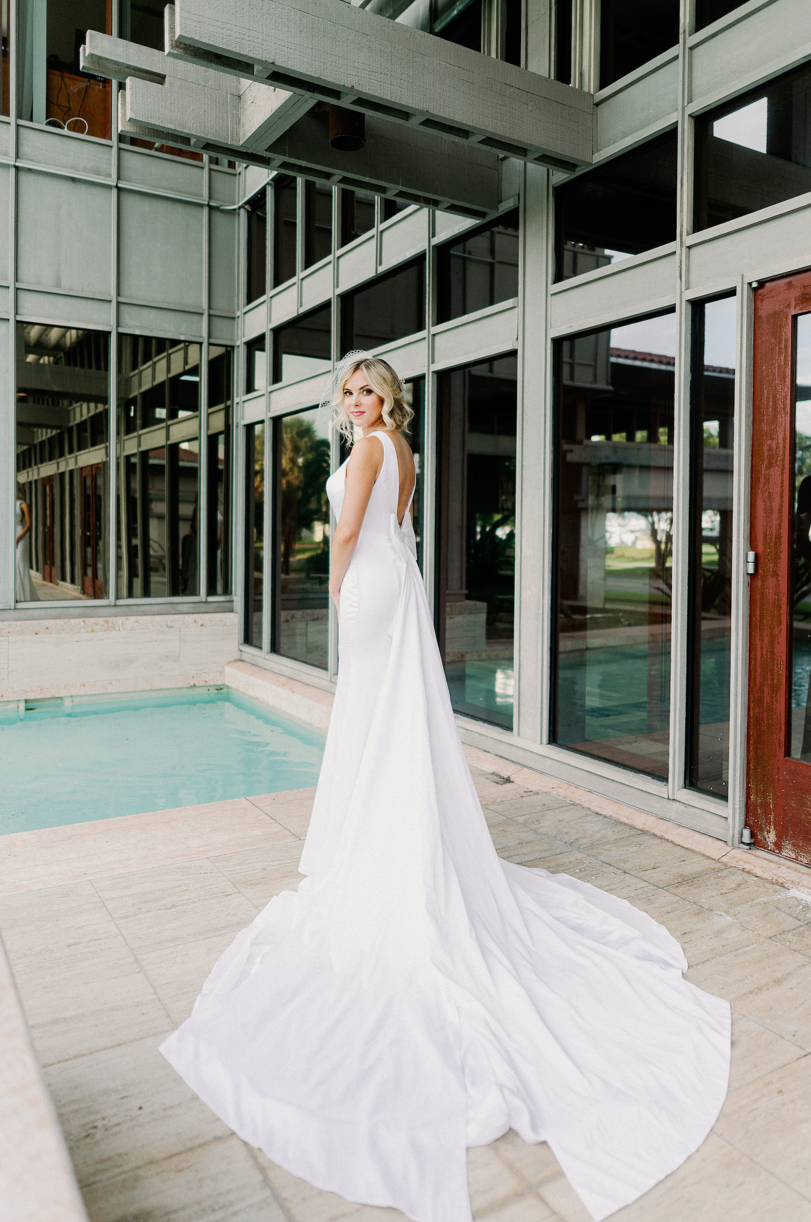 Outdoor Bridal Portrait at St. Pete Wedding Venue The Poynter Institute   LoAdoro Bridal Sleek Fitted Modern Wedding Dress Bridal Gown with Low Back and Detachable Bow Train with Birdcage Veil from Tampa Bridal Shop Truly Forever Bridal   Femme Akoi Beauty Studio   Dewitt for Love Photography