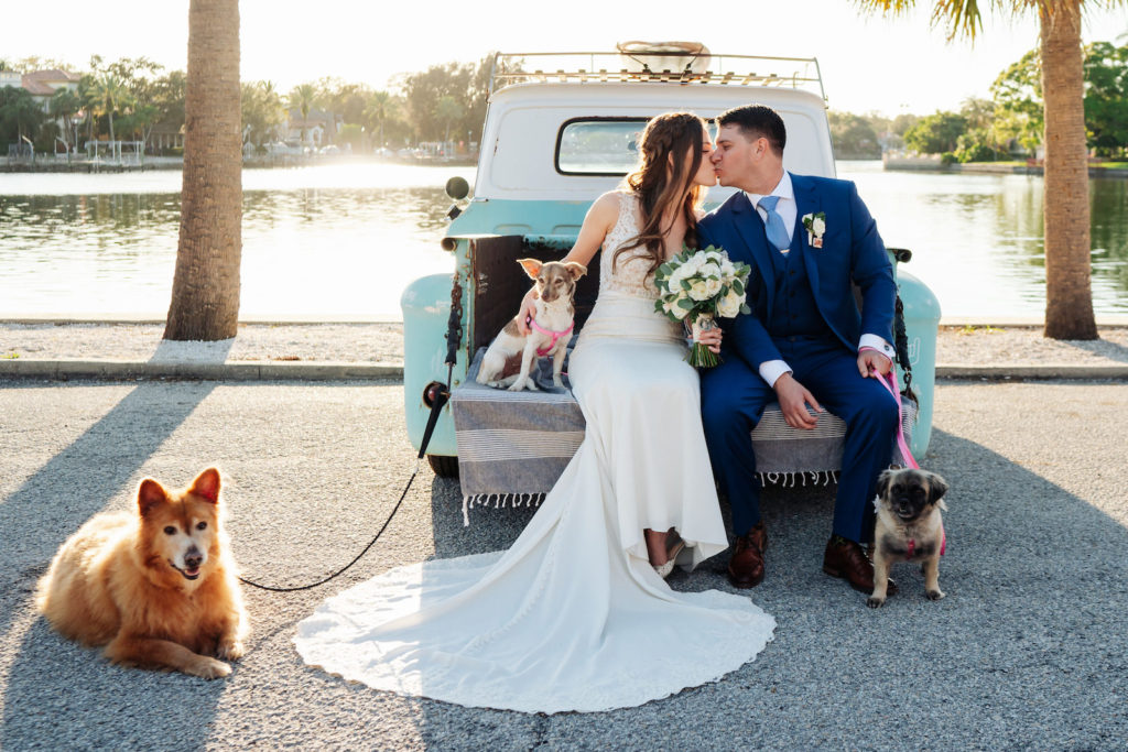 Tampa Bay Bride and Groom On Blue Vintage Rental Truck Outside of Lakefront Wedding Ceremony During Sunset, With Adoptable Senior Rescue Dogs, Bride Holding Modern Bridal Bouquet with Light Ivory and White Florals, Wearing Fitted Stella York Wedding Dress with Tan Bodice and White Lace Applique Overlay, Groom in Blue Men's Warehouse Tuxedo with Light Blue Tie | St. Petersburg Women's Club | Florida Day of Wedding Coordinator and Planner Special Moments Event Planning | Grind & Press Photography