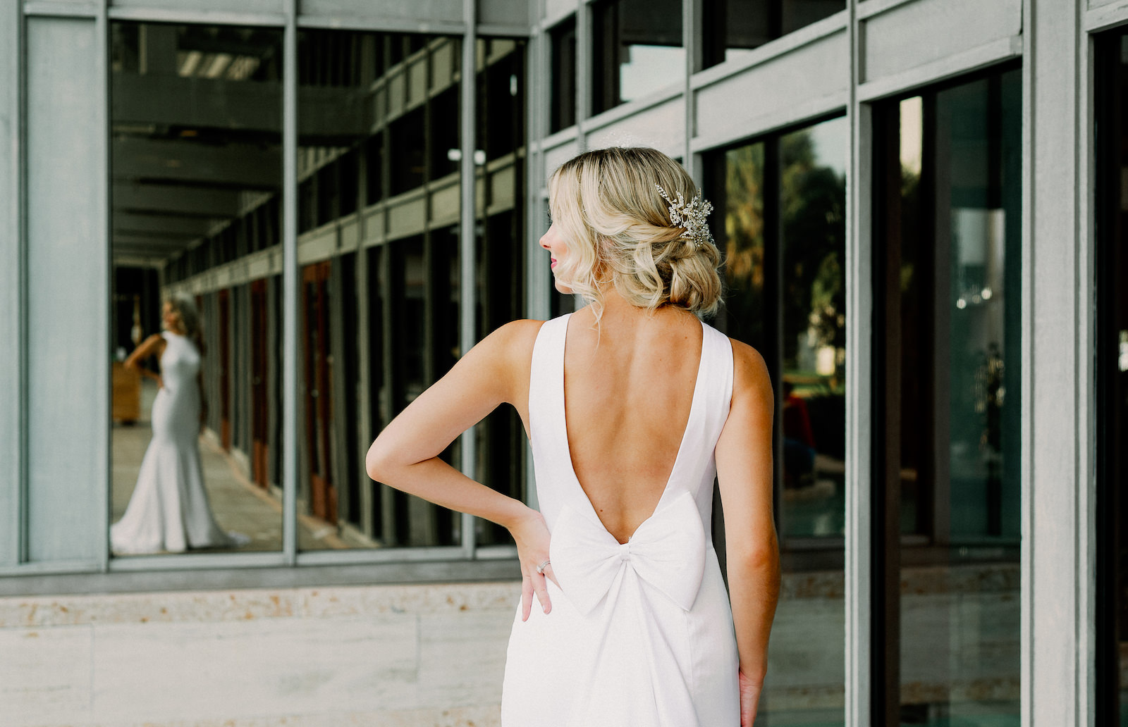 LoAdoro Bridal Sleek Fitted Modern Wedding Dress Bridal Gown with Low Back and Detachable Bow Train with Floral Hair Comb from Tampa Bridal Shop Truly Forever Bridal   Femme Akoi Beauty Studio   Dewitt for Love Photography