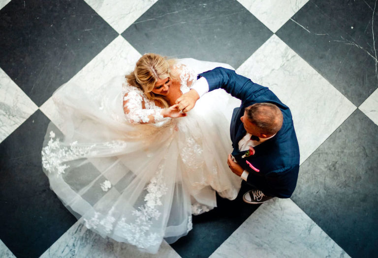 Intimate Portrait of Bride Tampa Bay Wedding Planner Katy from Coastal Coordinating and Groom Twirling New Wife on Black and White Checkered Floor | Wedding DJ Grant Hemond and Associates
