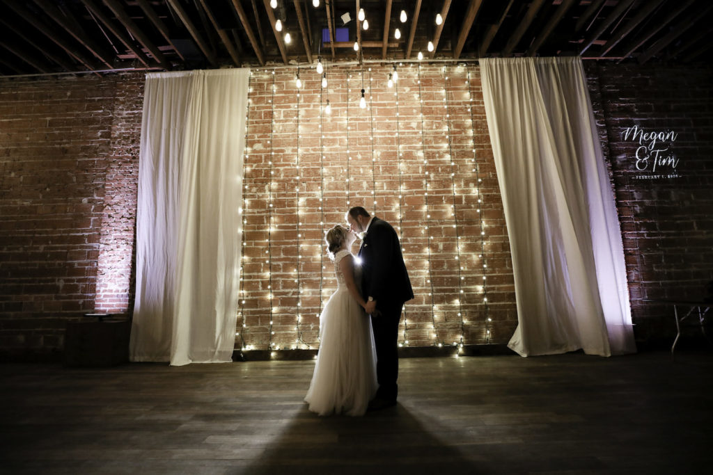 Modern, Simplistic Indoor Tampa Bay Wedding Ceremony, Downtown St. Petersburg Bride and Groom Exchange Vows With Exposed Brick Walls and Romantic String Lighting in Backdrop, White Draping, and Light Gobo of Custom Monogram | Florida Historic Wedding Venue NOVA 535 | St. Petersburg Wedding Photographer Lifelong Photography Studios
