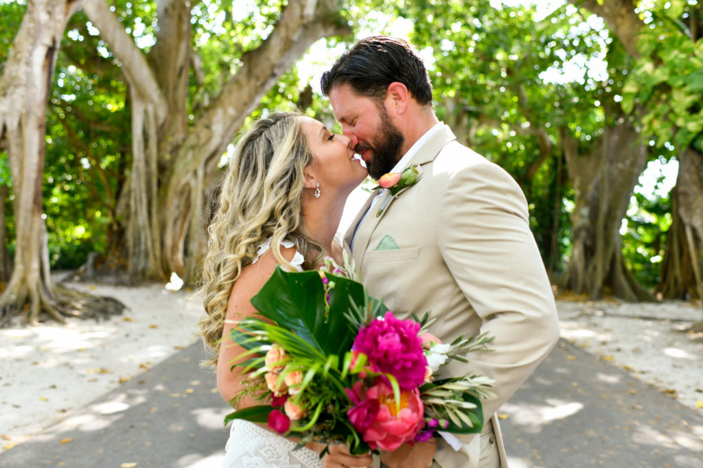 Tampa Bride Holding Fuchsia Pink, Peach and Monstera Palm Tree Leaves Tropical Floral Bouquet and Groom in Tan Suit