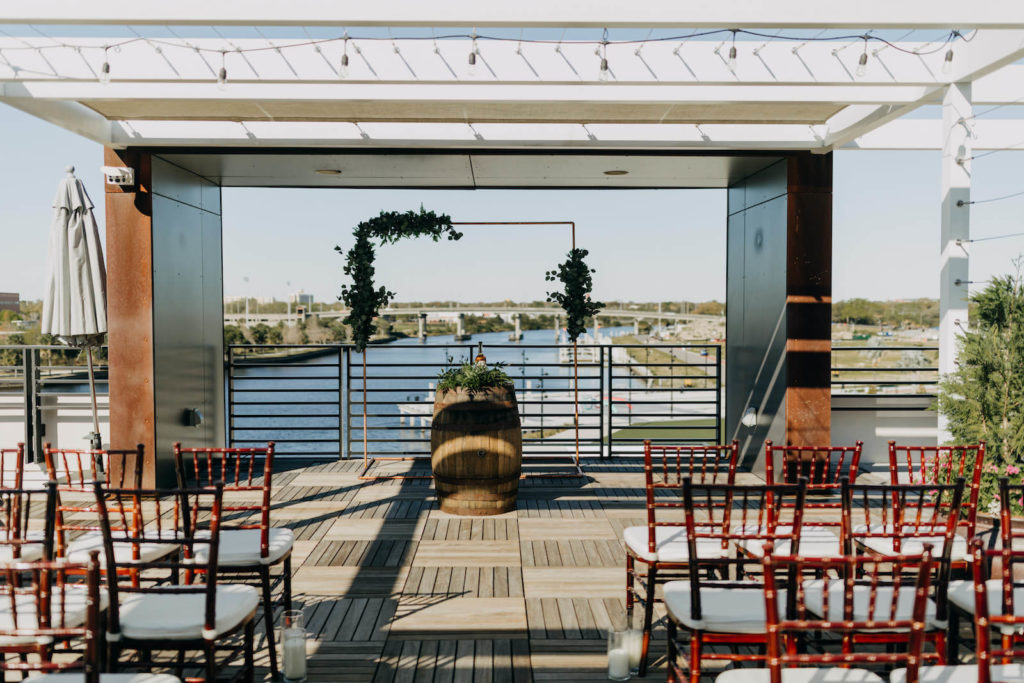 Downtown Tampa Heights Riverwalk Waterfront Wedding Ceremony at Rooftop 220 Armature Works | Copper Arch Ceremony Backdrop with Greenery Floral Arrangements and Jameson Whiskey Unity Ceremony | Whiskey Barrel from Tampa Event Rentals A Chair Affair | Mahogany Wood Chiavari Chairs with Ivory Cushions