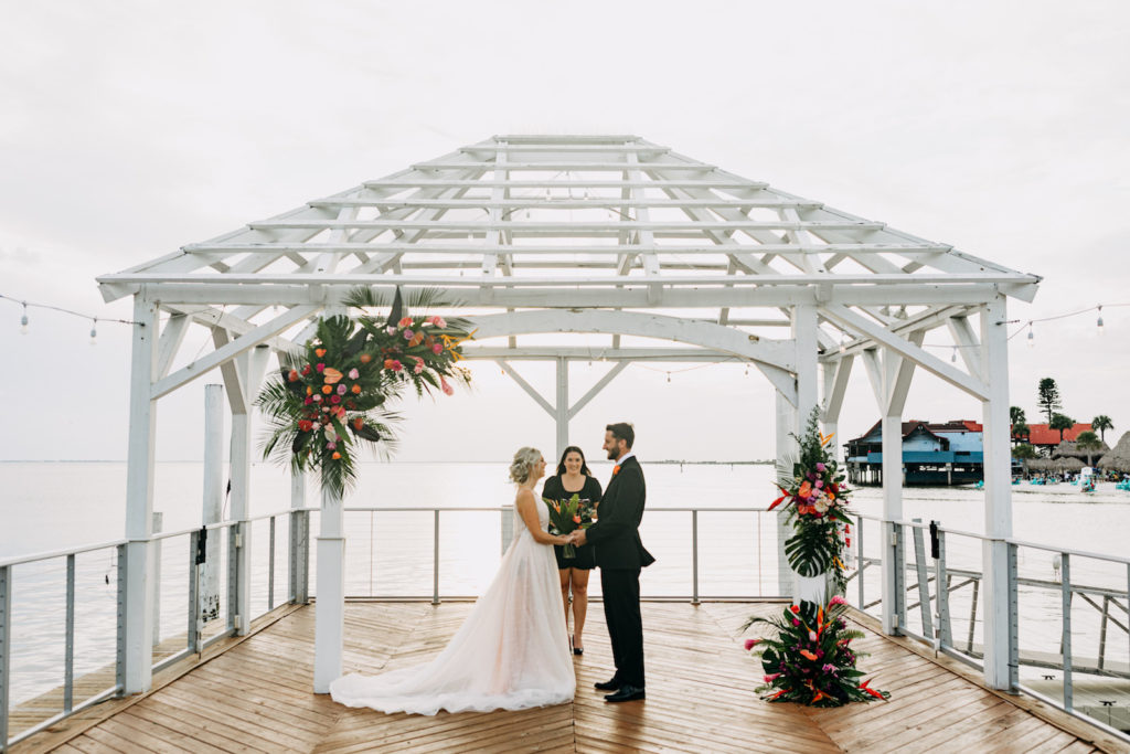 Groom and Bride Exchanging Wedding Vows Wearing Romantic Flowy Boho Wedding Dress, Open V Back on Waterfront Pier, Tropical Colorful Floral Arrangements, Styled Shoot | Tampa Bay Wedding Venue The Godfrey | Wedding Planner Elope Tampa Bay | Wedding Dress Nikki's Glitz and Glam | Wedding Florist Brides N Blooms | Amber McWhorter Photography