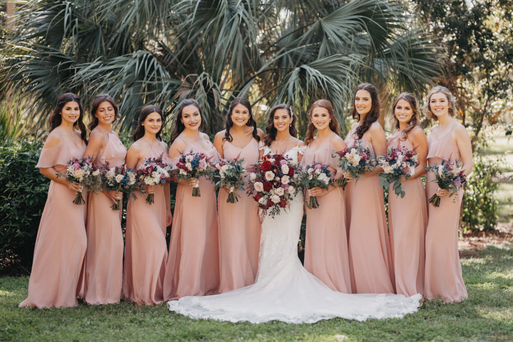 Florida bride with bridesmaids in mix and match pink dresses holding berry colored red, purple, pink and blush rose floral bouquets | Tampa Bay wedding hair and makeup Michele Renee the Studio | Wedding Planner Special Moments Event Planning