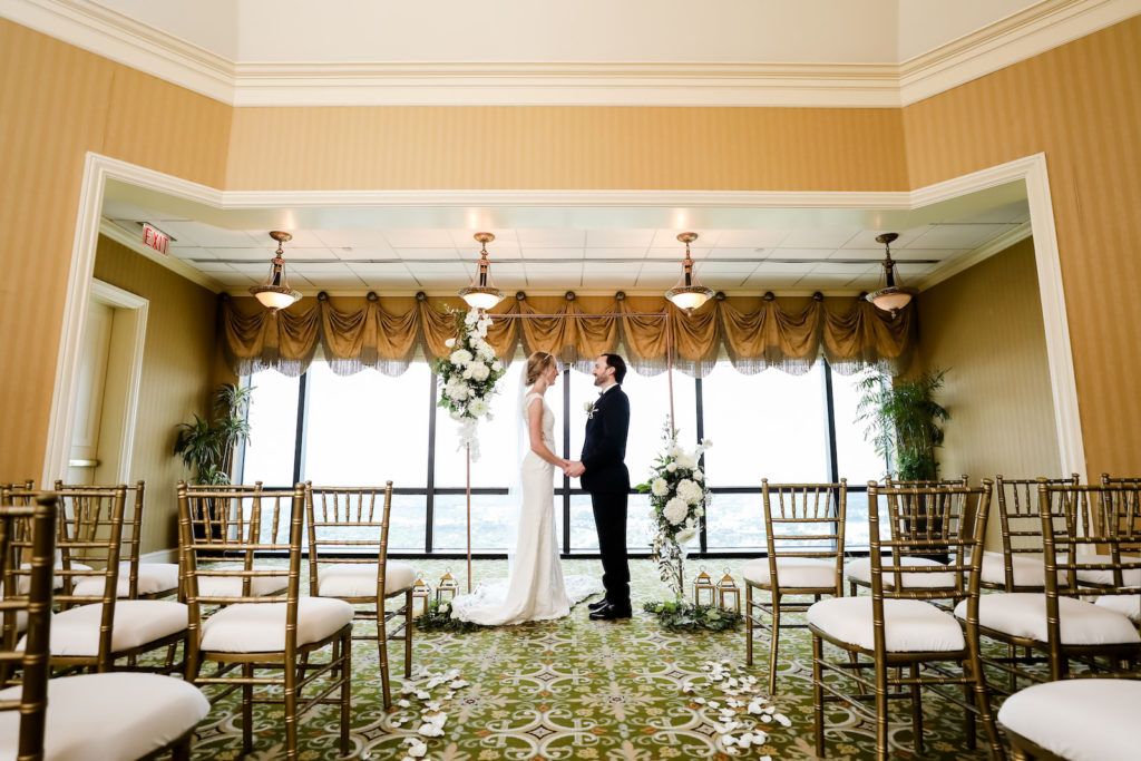 Classic Bride and Groom Exchanging Wedding Vows During Ceremony, Rectangular Arch with White and Greenery Lush Floral Arrangements, Gold Chiavari Chairs | Tampa Bay Wedding Planner Elegant Affairs by Design | Wedding Venue The Tampa Club | Wedding Photographer Lifelong Photography Studio | Wedding Rentals Outside the Box Event Rentals | Wedding Dress and Tuxedo Truly Forever Bridal | Styled Shoot