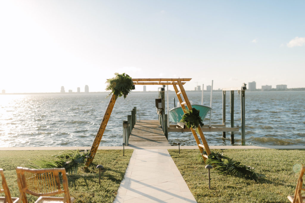 Tropical Modern Waterfront Wedding Ceremony Decor, Bamboo Ladder Arch with Monstera Palm Tree Leaf Arrangements | Tampa Bay Wedding Planner, Florist and Designer John Campbell Weddings