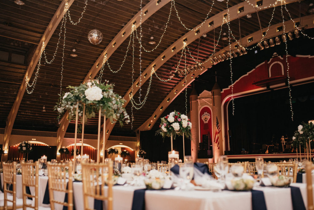 Traditional romantic wedding reception decor, hanging draped lights, gold chiavari chairs, tall floral centerpieces navy blue linens | Tampa Bay wedding planner Special Moments Events | Wedding Venue St. Pete Coliseum