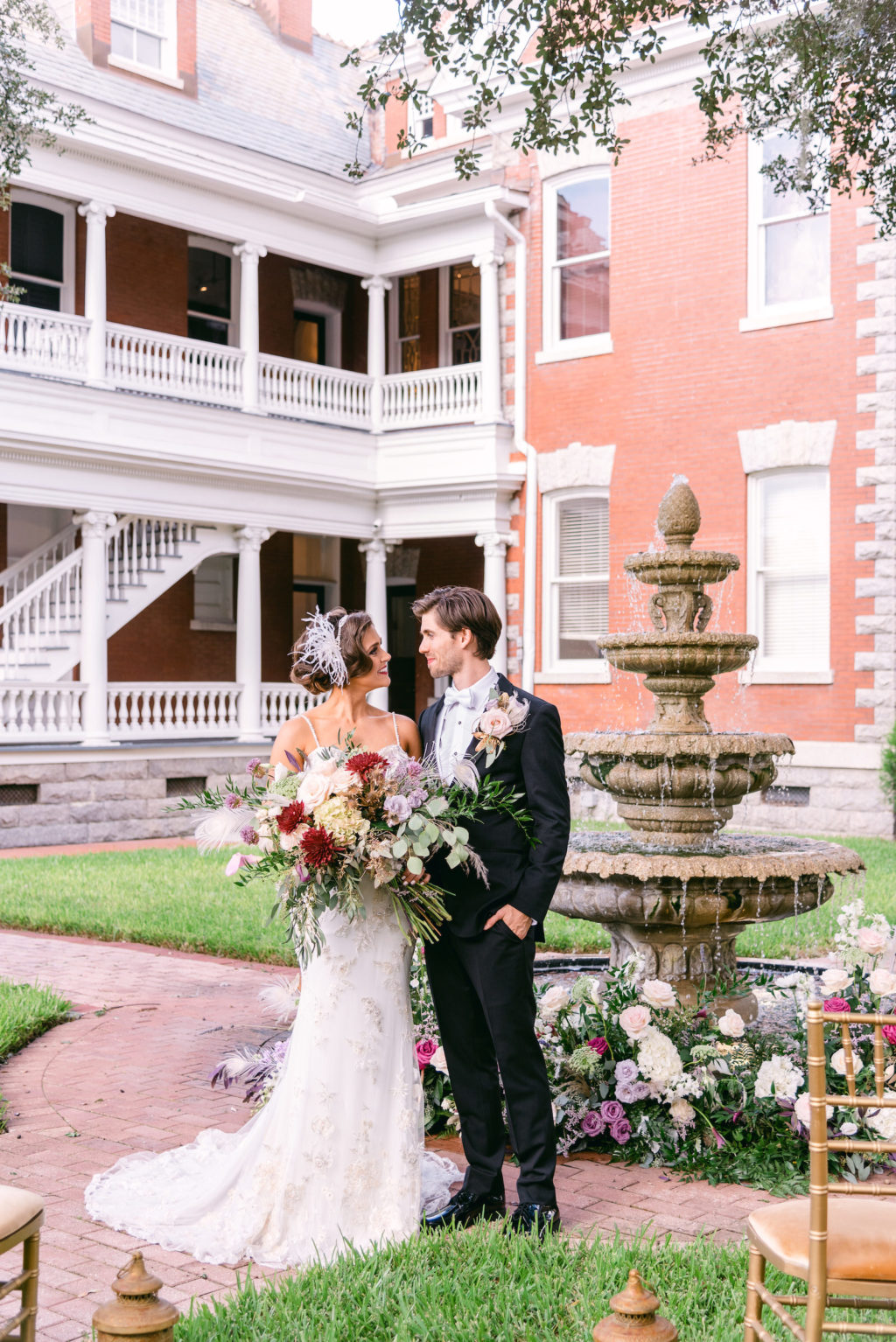 Florida Bride and Groom in Courtyard of Historic Wedding Venue Anderson House, Bride Wearing Lace Wedding Dress Holding Lush Whimsical Purple, Red, White Florals, Feathers, Greenery Bouquet | Tampa Bay Wedding Planner EventFull Weddings