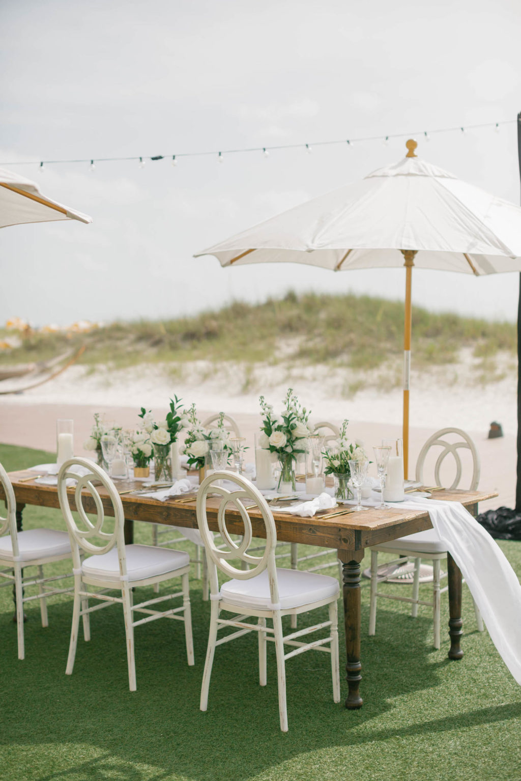 Garden-style beachside wedding reception decor, wooden farm feasting table with white table runner, white chairs, umbrellas, and floral centerpieces | Tampa Bay wedding planner Parties A'la Carte | Kate Ryan Event Rentals | Clearwater Beach Wedding Venue Sandpearl Resort