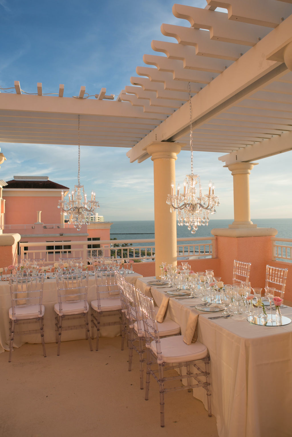 Elegant Modern Wedding Reception Decor on Rooftop Balcony of Waterfront Wedding Venue Hyatt Regency Clearwater Beach, Long Tables with Acrylic Chiavari Chairs, Hanging Crystal Chandeliers | Tampa Bay Wedding Photographer Carrie Wildes | Wedding Planner Coastal Coordinating | Wedding Rentals Outside the Box