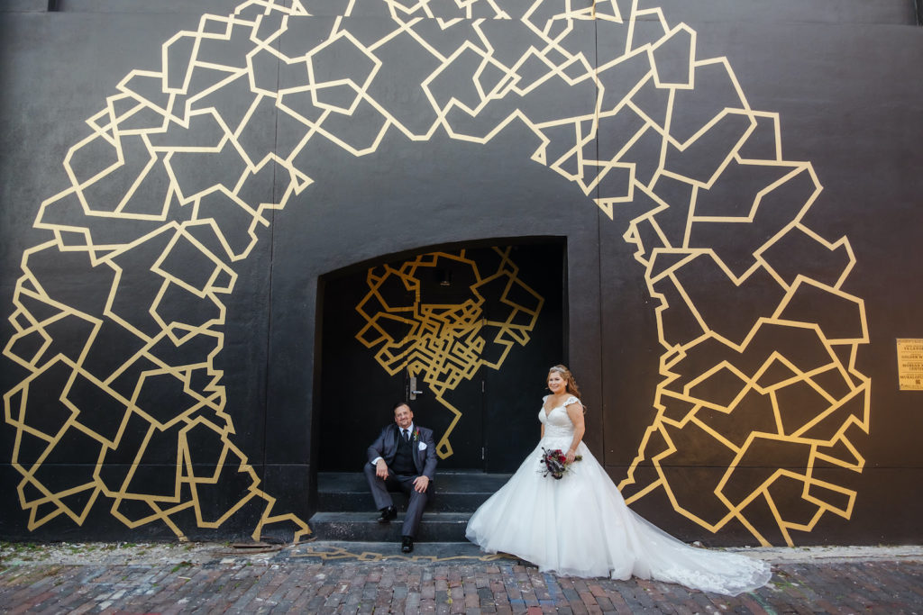 Halloween Bride and Groom Outside Black Building with Gold Whimsical Painted Geometric Shapes, Bride in Lace and Tulle Capsleeve Ballgown Wedding Dress   Tampa Bay Wedding Dress Shop Truly Forever Bridal