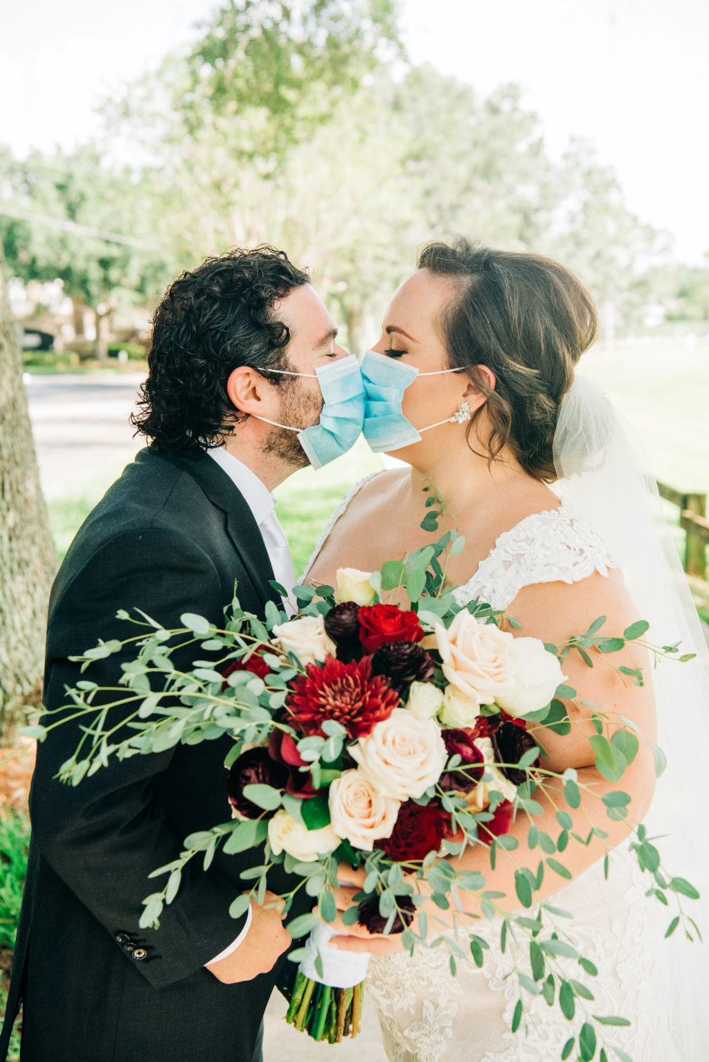 Intimate Backyard COVID Wedding | Bride and Groom Portrait with Face Masks | Lace Aline Martina Liana Wedding Dress Bridal Gown with Cathedral Veil | Groom in Classic Black Tux by Indochino | Red White and Blue Wedding Bouquet with Roses Ranunculus and Greenery
