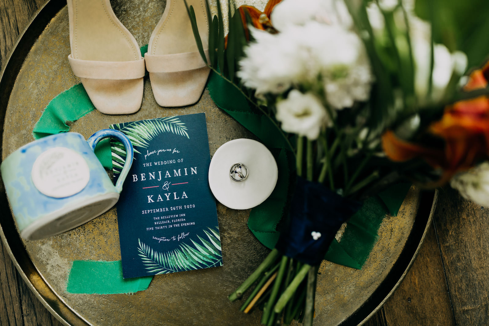 Navy Blue and Green Clearwater Tropical Wedding Invitation with Palm Frond Leaf   Wedding Ring Shot Flat Lay with Bridal Accessories Bouquet and Shoes   Amber McWhorter Photography