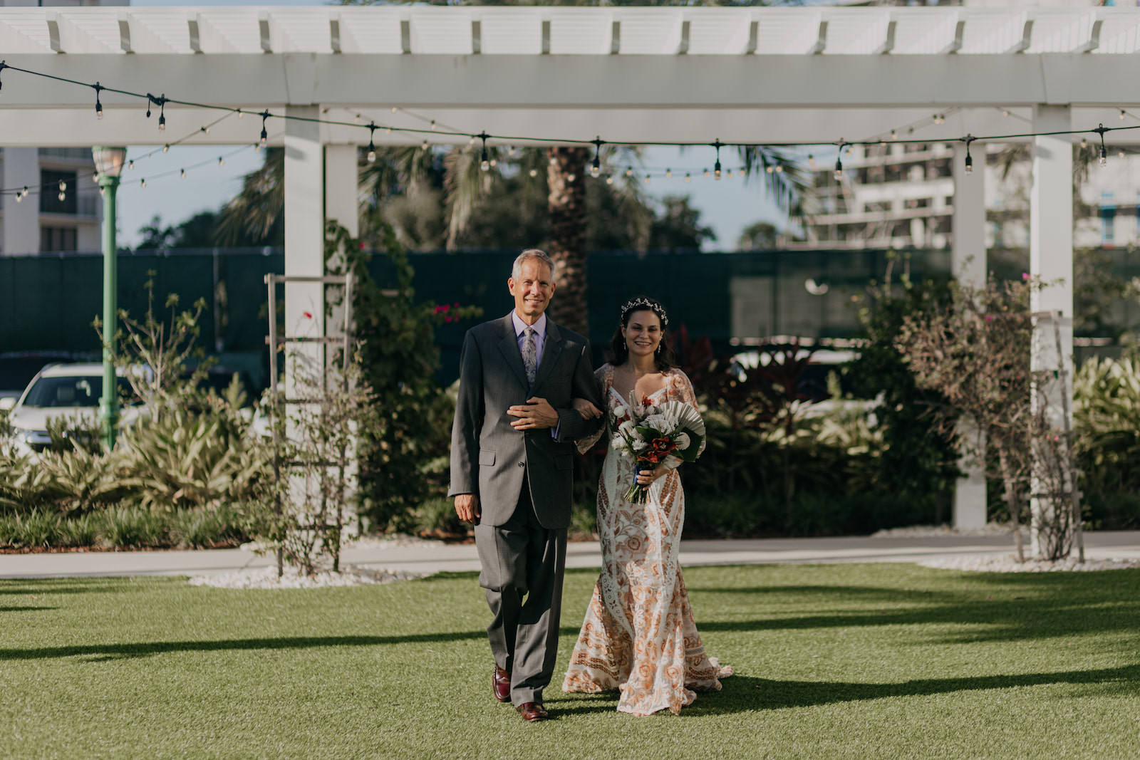 Bride Walking Down Aisle with Father during Outdoor Clearwater Wedding Ceremony   Boho Gold Bronze Embroidered Overlay Wedding Dress Bridal Gown with Illusion Sleeves and Train   Tropical Boho Bridal Bouquet