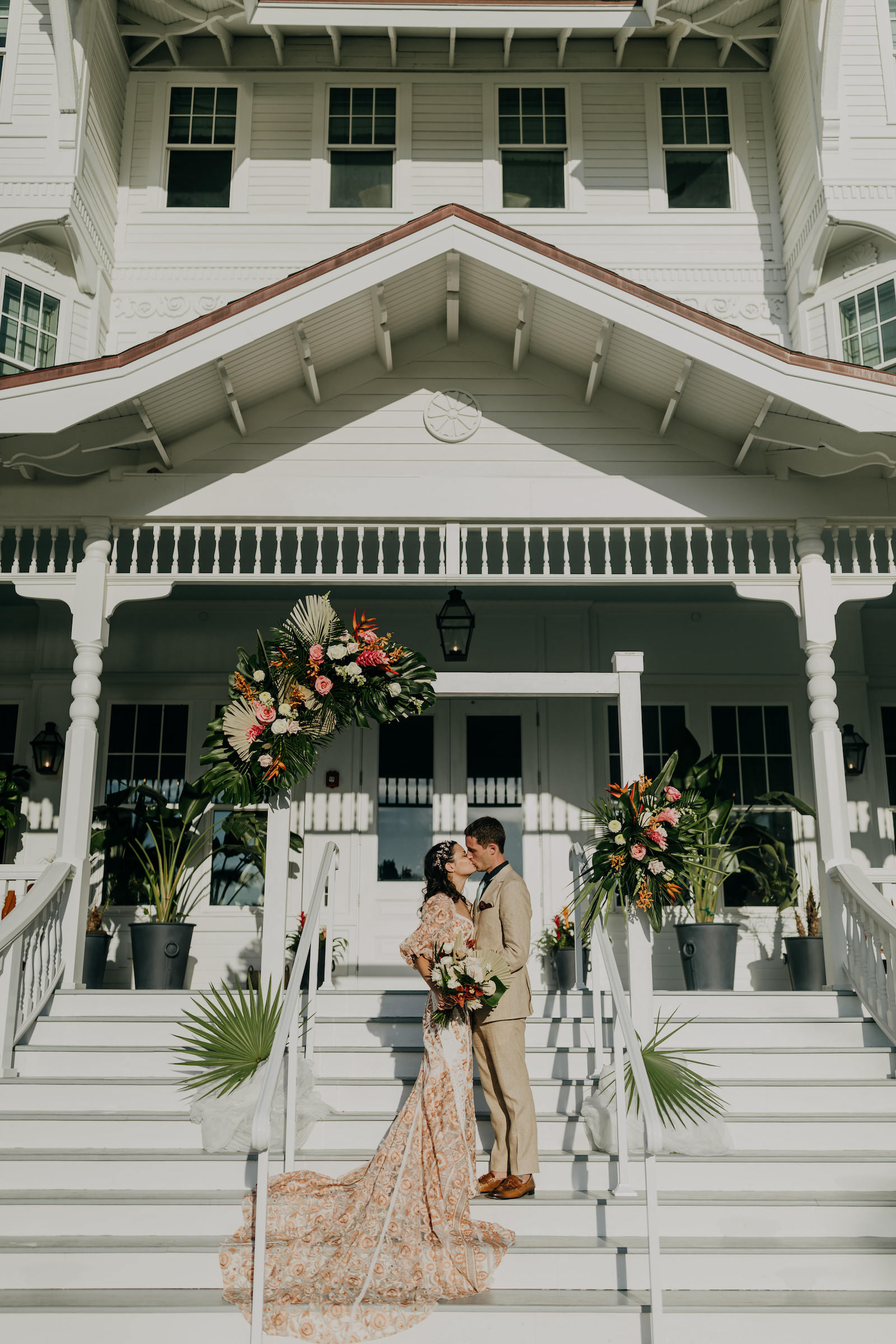 Outdoor Staircase Wedding Ceremony Bride and Groom Portrait on Belleview Inn Staircase   Boho Gold Bronze Embroidered Overlay Wedding Dress Bridal Gown with Illusion Sleeves and Train   Groom in Grey Khaki Linen Suit   Tropical Boho Bridal Bouquet and White Arch Backdrop with Palm Frond Leaf Coral Orange Pink and Greenery Floral Arrangements   Amber McWhorter Photography