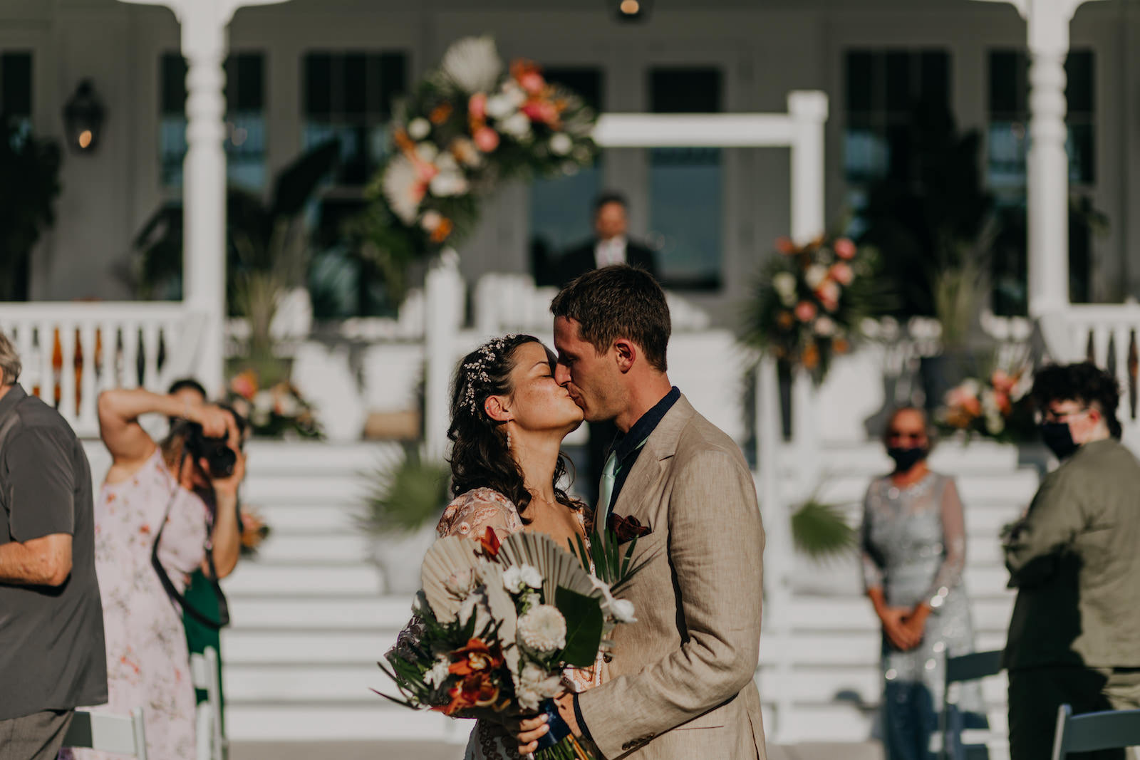 Outdoor Staircase Wedding Ceremony Bride and Groom Portrait on Belleview Inn Staircase   Boho Gold Bronze Embroidered Overlay Wedding Dress Bridal Gown with Illusion Sleeves and Train   Groom in Grey Khaki Linen Suit   Tropical Boho Bridal Bouquet and White Arch Backdrop with Palm Frond Leaf Coral Orange Pink and Greenery Floral Arrangements