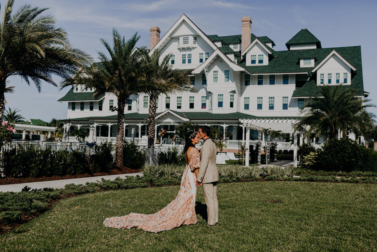 Outdoor Bride and Groom Wedding Portrait at Historic Clearwater Venue Belleview Inn   Boho Gold Bronze Embroidered Overlay Wedding Dress Bridal Gown with Illusion Sleeves and Train   Groom in Grey Khaki Linen Suit