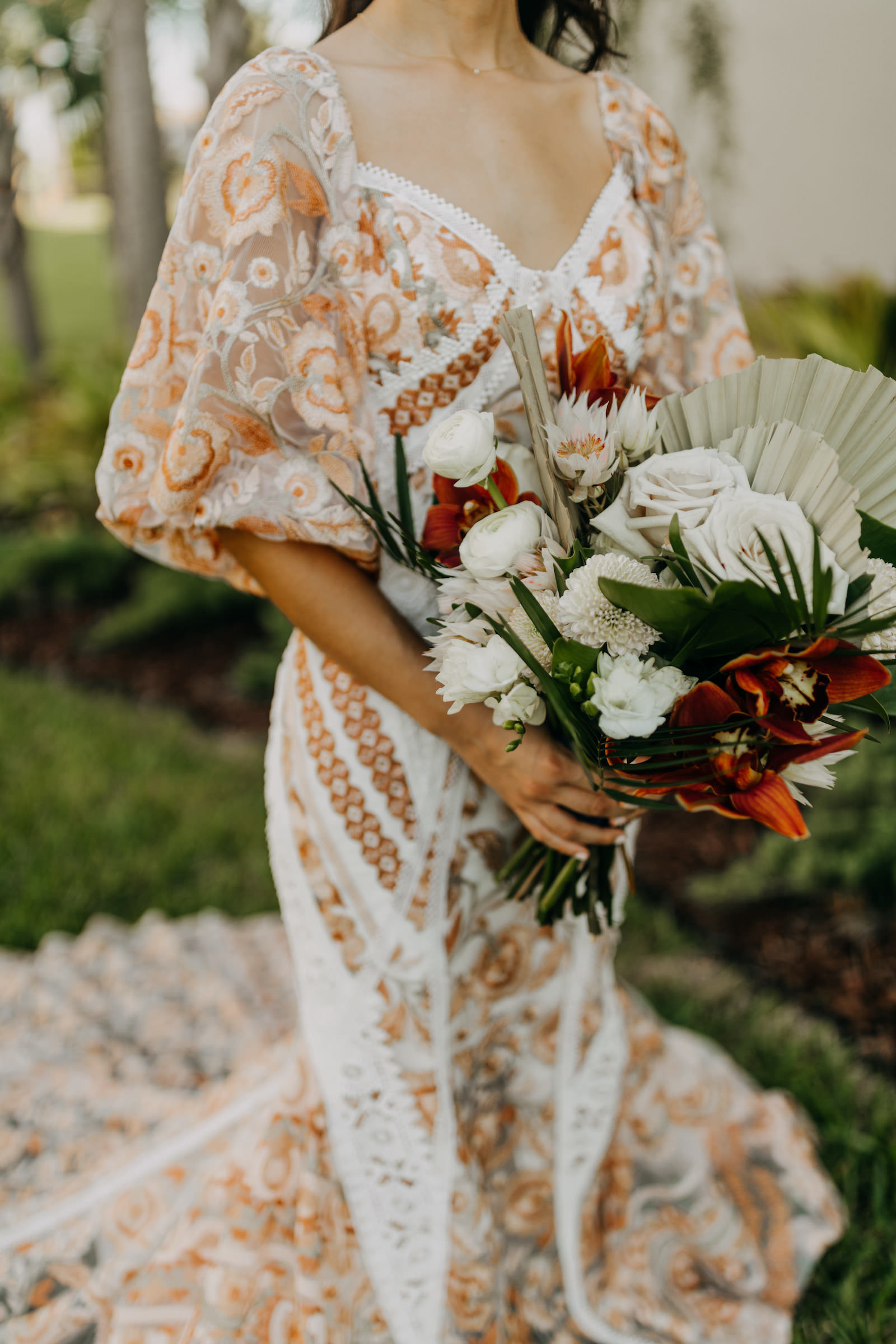 Boho Gold Bronze Embroidered Overlay Wedding Dress Bridal Gown with Illusion Sleeves and Train   Tropical Boho Bridal Bouquet with White Roses Orange Orchids and Palm Frond Leaves   Amber McWhorter Photography