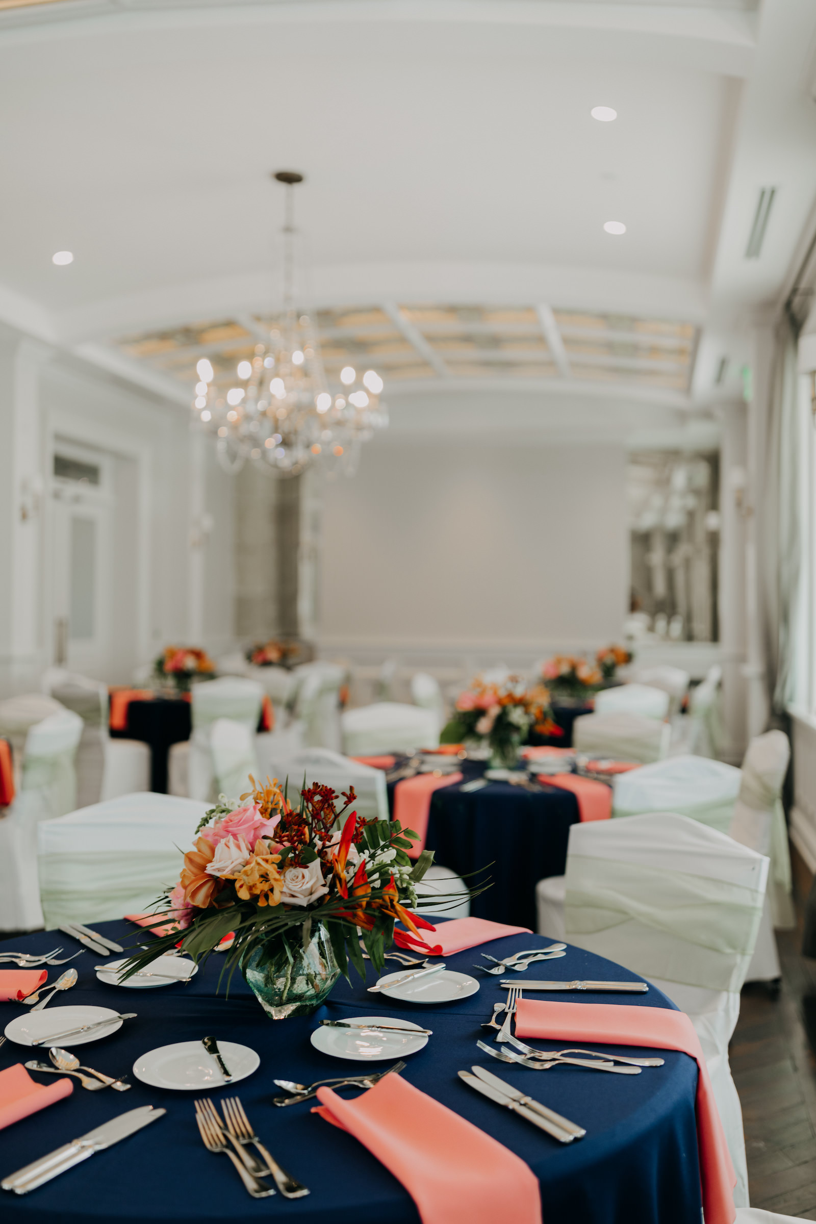 Indoor Clearwater Wedding Reception At Historic Venue Hotel Navy Blue Reception Table With Coral Peach Pink Napkins And Tropical Floral Arrangement Centerpieces Marry Me Tampa Bay Local Real Wedding