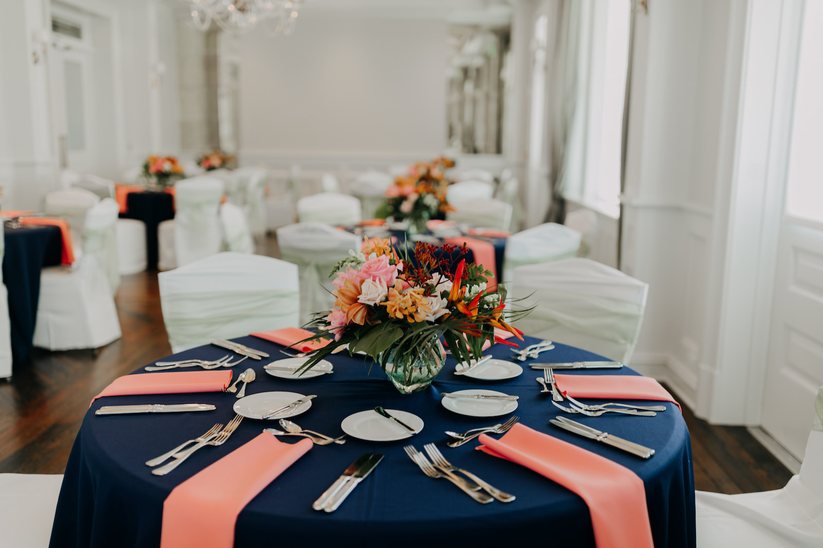 Indoor Clearwater Wedding Reception at Historic Venue Hotel   Navy Blue Reception Table with Coral Peach Pink Napkins and Tropical Floral Arrangement Centerpieces