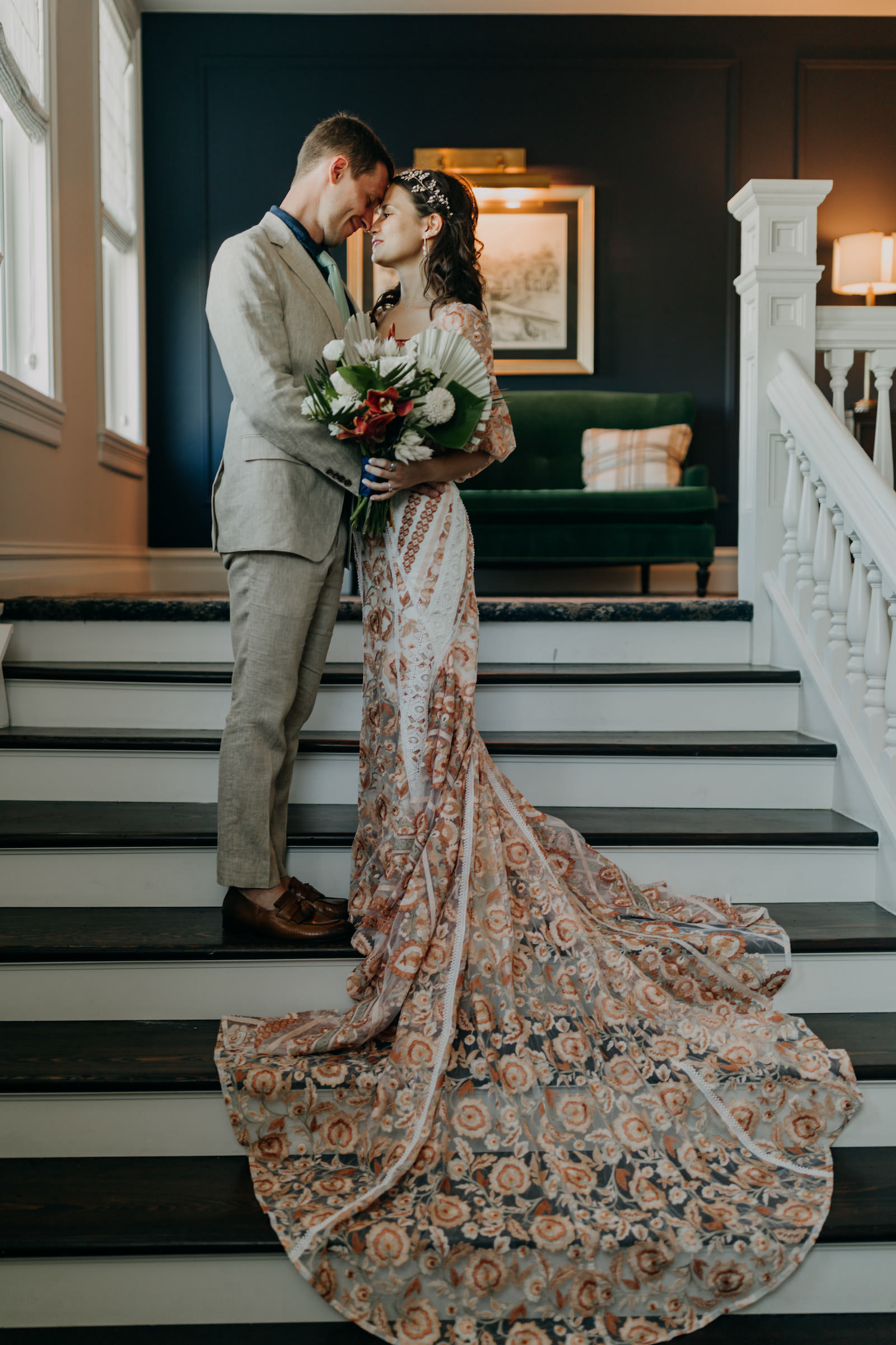 Indoor Bride and Groom Portrait on Staircase   Boho Gold Bronze Embroidered Overlay Wedding Dress Bridal Gown with Illusion Sleeves and Train   Groom in Grey Khaki Linen Suit   Tropical Boho Bridal Bouquet   Amber McWhorter Photography