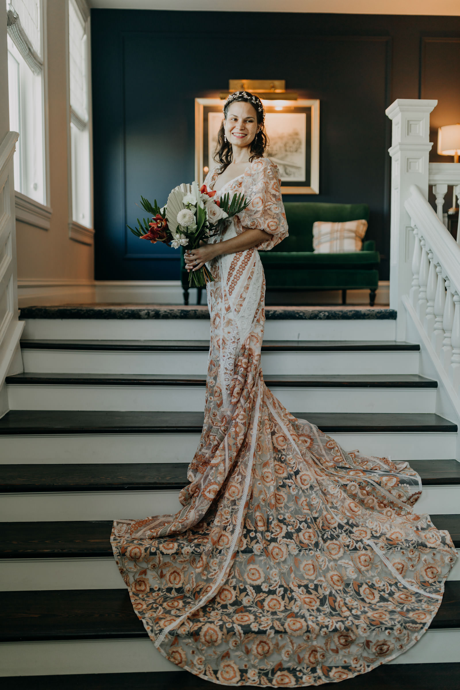 Indoor Bridal Portrait on Staircase   Boho Gold Bronze Embroidered Overlay Wedding Dress Bridal Gown with Illusion Sleeves and Train   Tropical Boho Bridal Bouquet   Amber McWhorter Photography