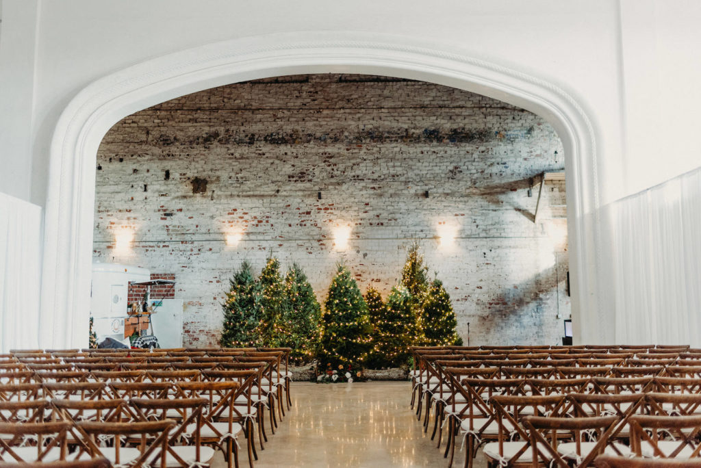 Indoor Tampa Christmas Wedding Ceremony with Wood Cross Back Chairs and Lit Christmas Tree Backdrop