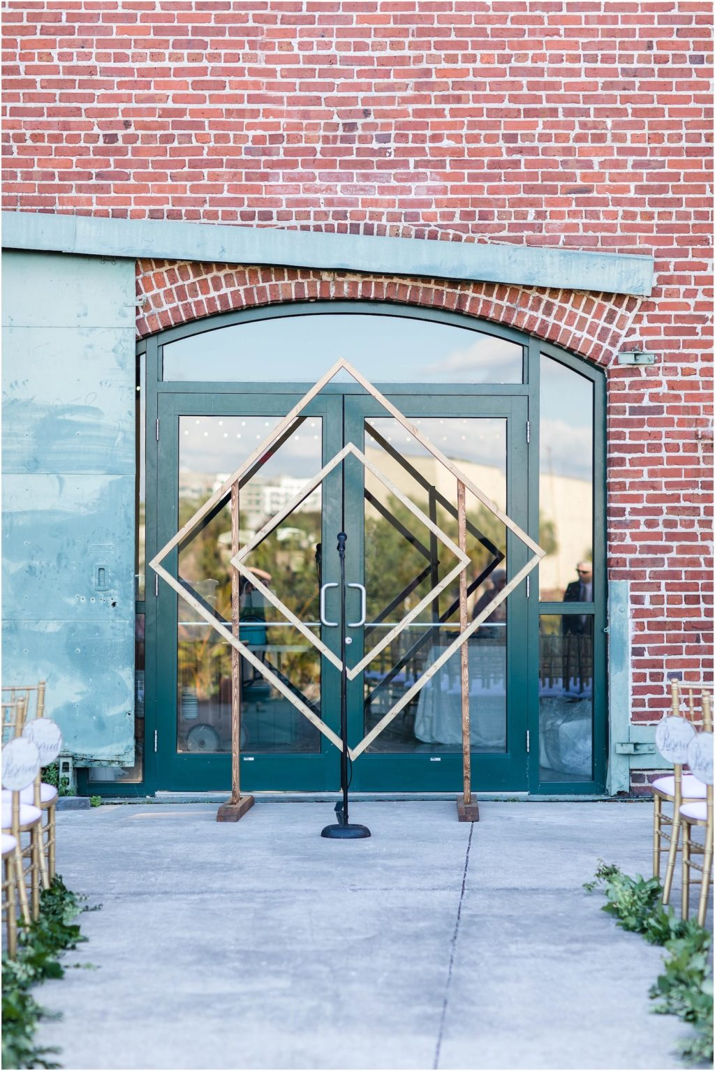 Industrial Geometric Square Wedding Arch Backdrop with Historic Brick Wall Building