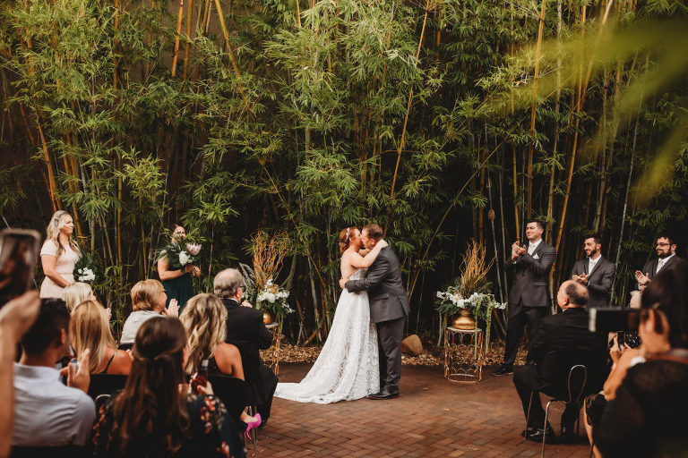 Modern Tropical Inspired Florida Wedding Ceremony in Bamboo Garden, DIY Floral Centerpieces with Bronze Base and Greenery, Bride and Groom Exchanging First Kiss During Outdoor Ceremony | Downtown St. Pete Historic Wedding Venue NOVA 535 - Courtyard