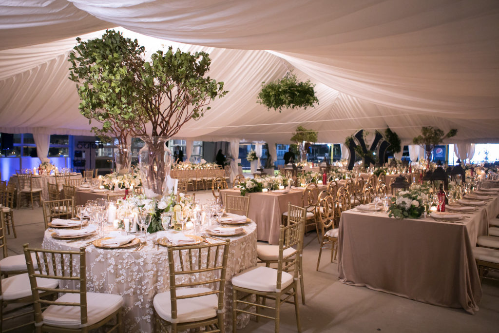 Green and White Tampa Wedding Reception at Steinbrenner Field Tampa Yankees | Tented Reception with Draped Ceiling and Greenery Chandelier | Champagne Table Linens with Gold Chargers, Louis Chairs and Chiavari Chairs and Tree Branch Centerpieces