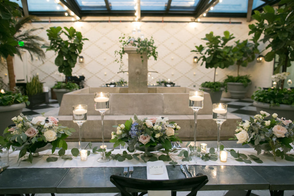 Indoor Downtown Tampa Wedding Reception in Historic Building Restaurant Atrium Greenhouse with Fountain | Metal Banquet Tables with Eucalyptus Greenery Branches and Floating Candles with Blush Pink and Blue Centerpiece Floral Arrangements