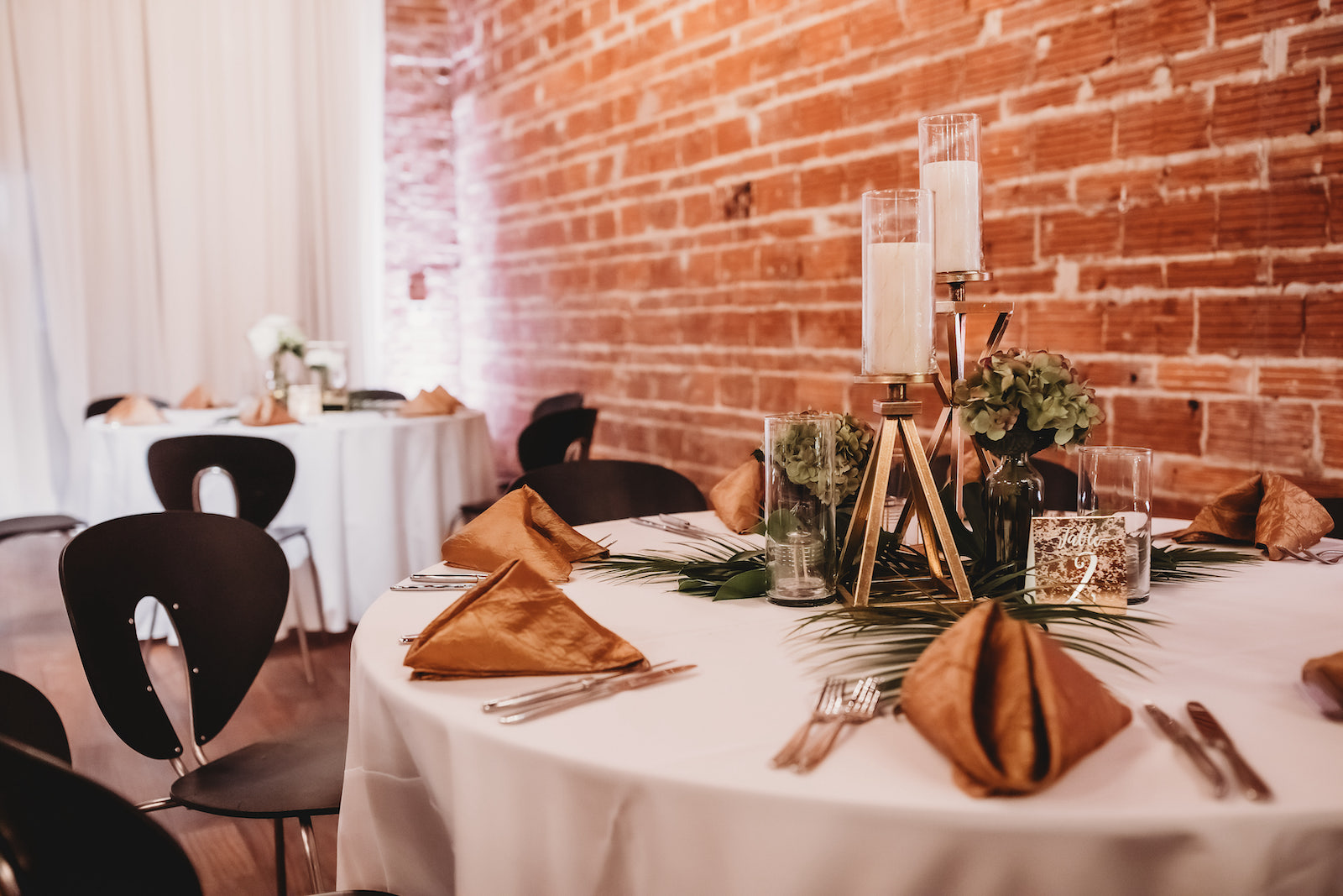 Modern Tropical Florida Wedding Reception And Decor Round Tables With Gold Napkin Linens Palm Leaf Greenery And Low Floral Centerpieces With Geometric Vase Exposed Red Brick Wall Unique Tampa Bay Wedding