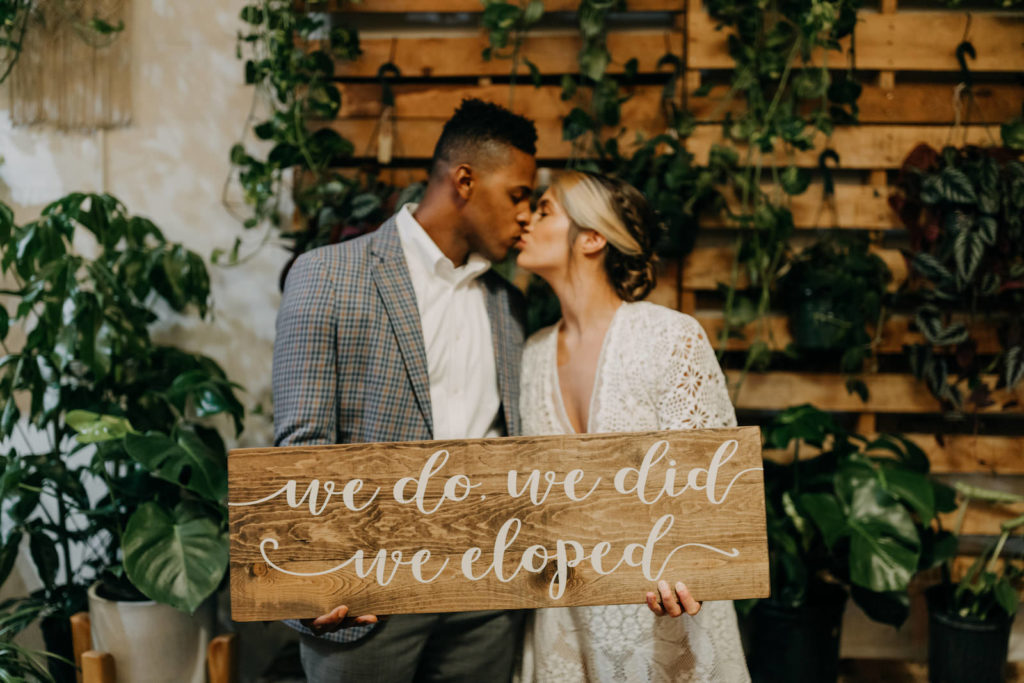 Boho Neutral Styled Shoot | Bride in Vintage Lace Fringe Short Sleeve V Neckline Wedding Dress Groom in Blue Plaid Suit with Greenery Plants | Unique St. Pete Wedding Venue Wild Roots Nursery | Amber McWhorter Photography | Wedding Planner Elope Tampa Bay