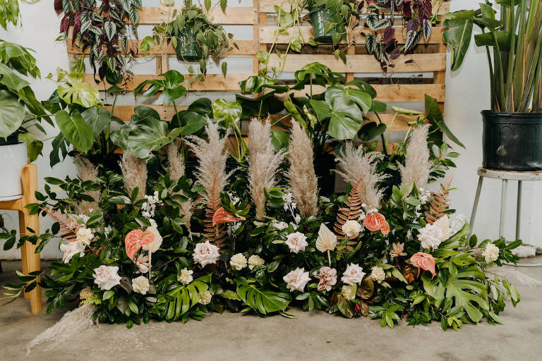 Boho Neutral Styled Shoot Decor | Wooden Pallets with Hanging Greenery Plants, Monstera Palm Trees, Floral Arrangements with Pampas Grass, Ivory Roses, Pink Anthurium | St. Pete Wedding Venue Wild Roots | Amber McWhorter Photography | Wedding Planner Elope Tampa Bay