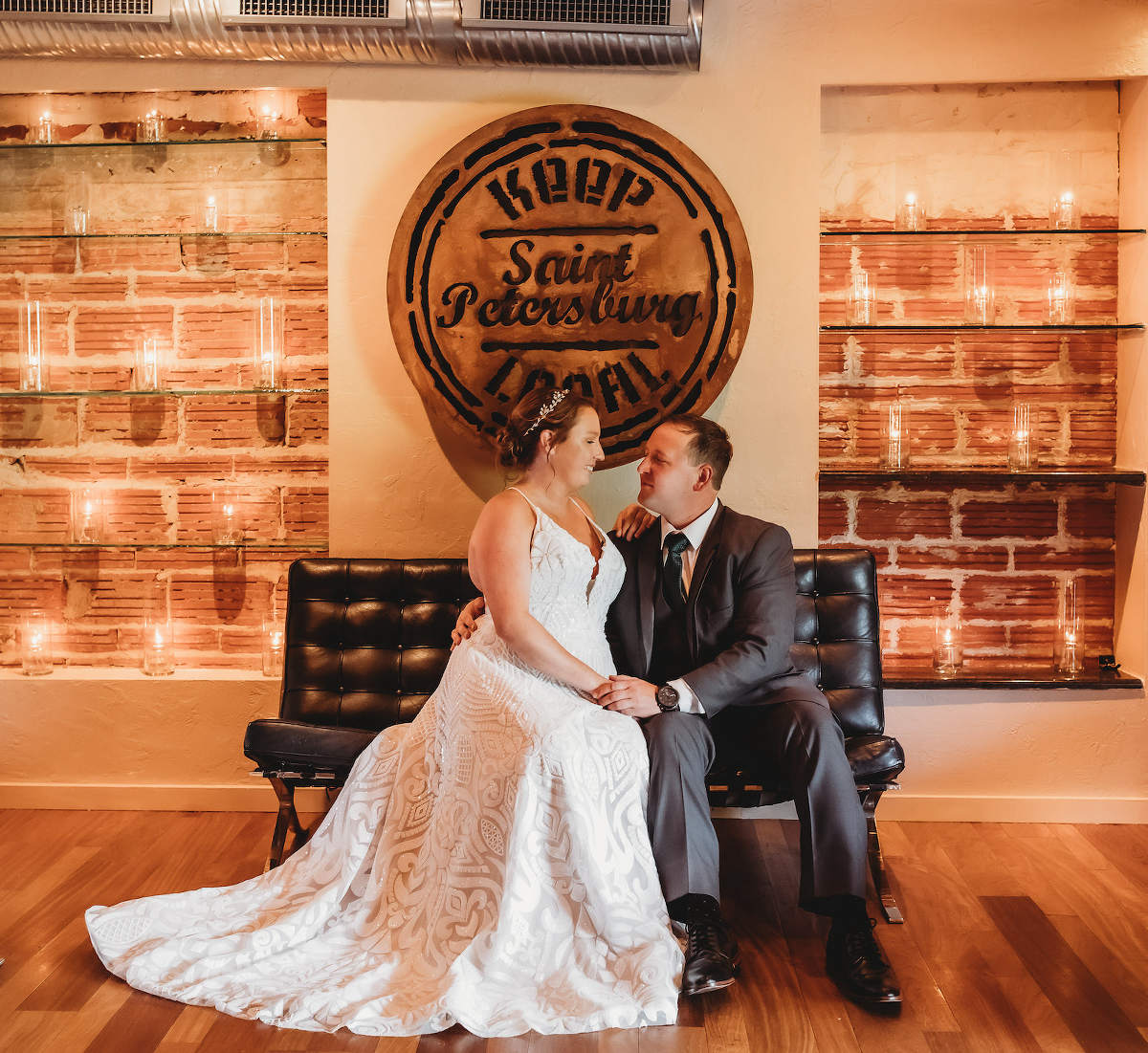 Florida Bride and Groom Romantic Wedding Portrait Inside Historic Venue in Downtown Saint Petersburg, Keep Local Custom Sign, Exposed Brick with Candlelight Lighting, Bride Wearing Blush By Hayley Paige Ivory Delta Gown Style 1751 | Unique Tampa Bay Wedding Venue NOVA 535 in Downtown St. Petersburg